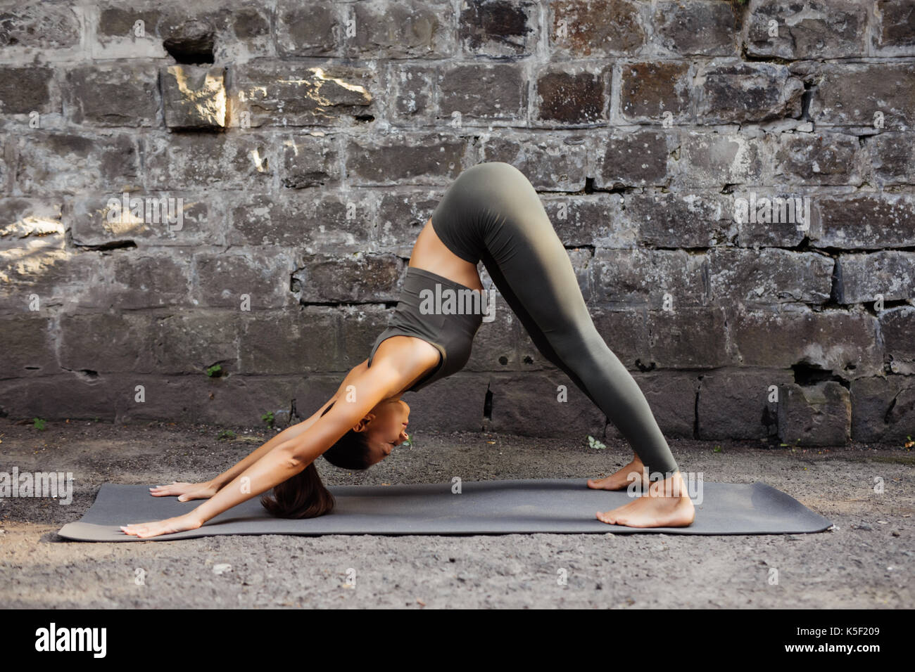 Woman practicing yoga against a brick wall - Stock Image
