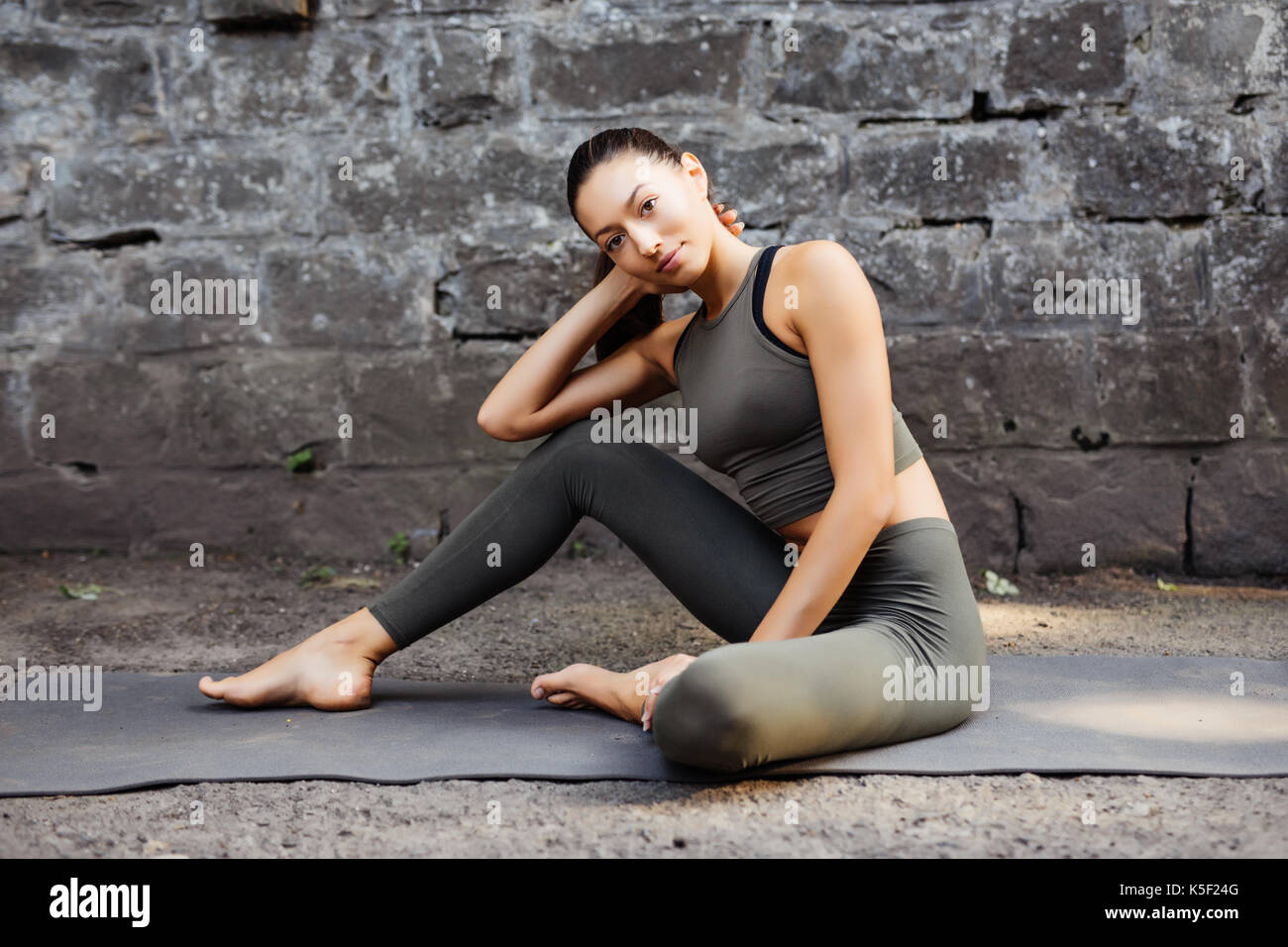 Sporty beautiful young woman practicing yoga working out, wearing sportswear, outdoor full length, brick wall - Stock Image
