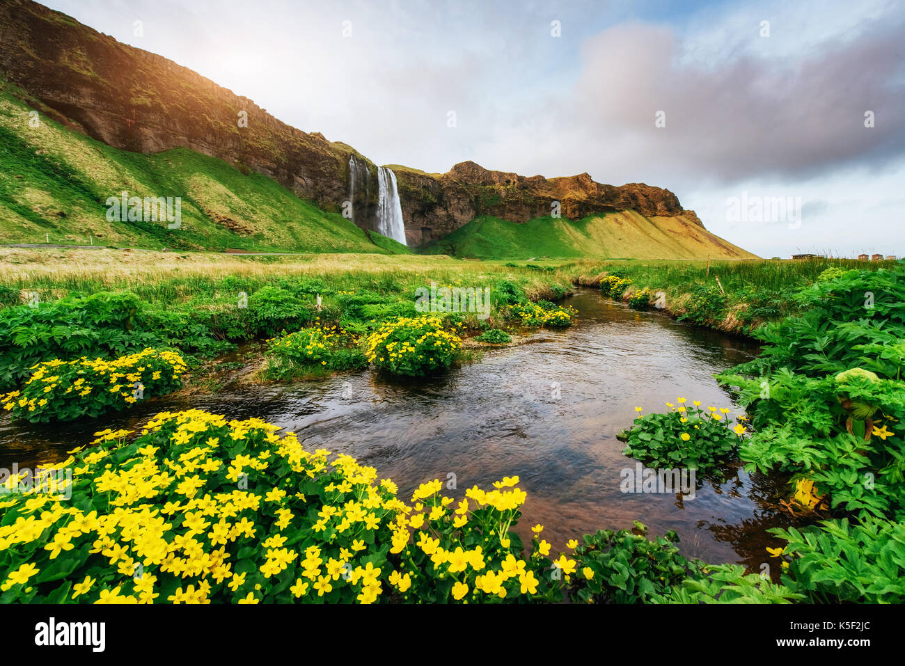 Seljalandfoss waterfall at sunset. Bridge over the river. Fantastic nature. Iceland - Stock Image