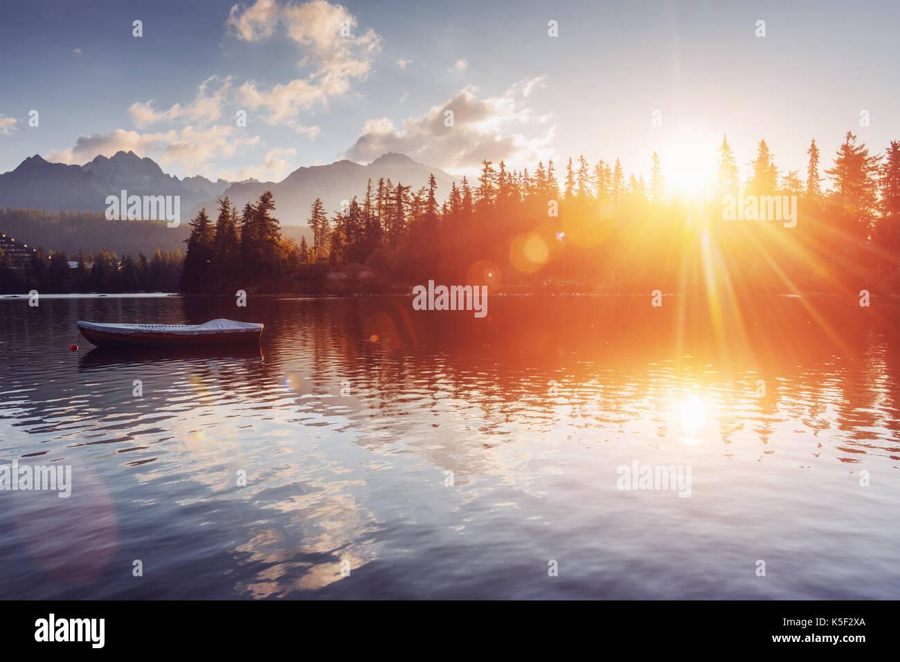 The sunrise over a lake in the park High Tatras. Shtrbske Pleso, Slovakia - Stock Image