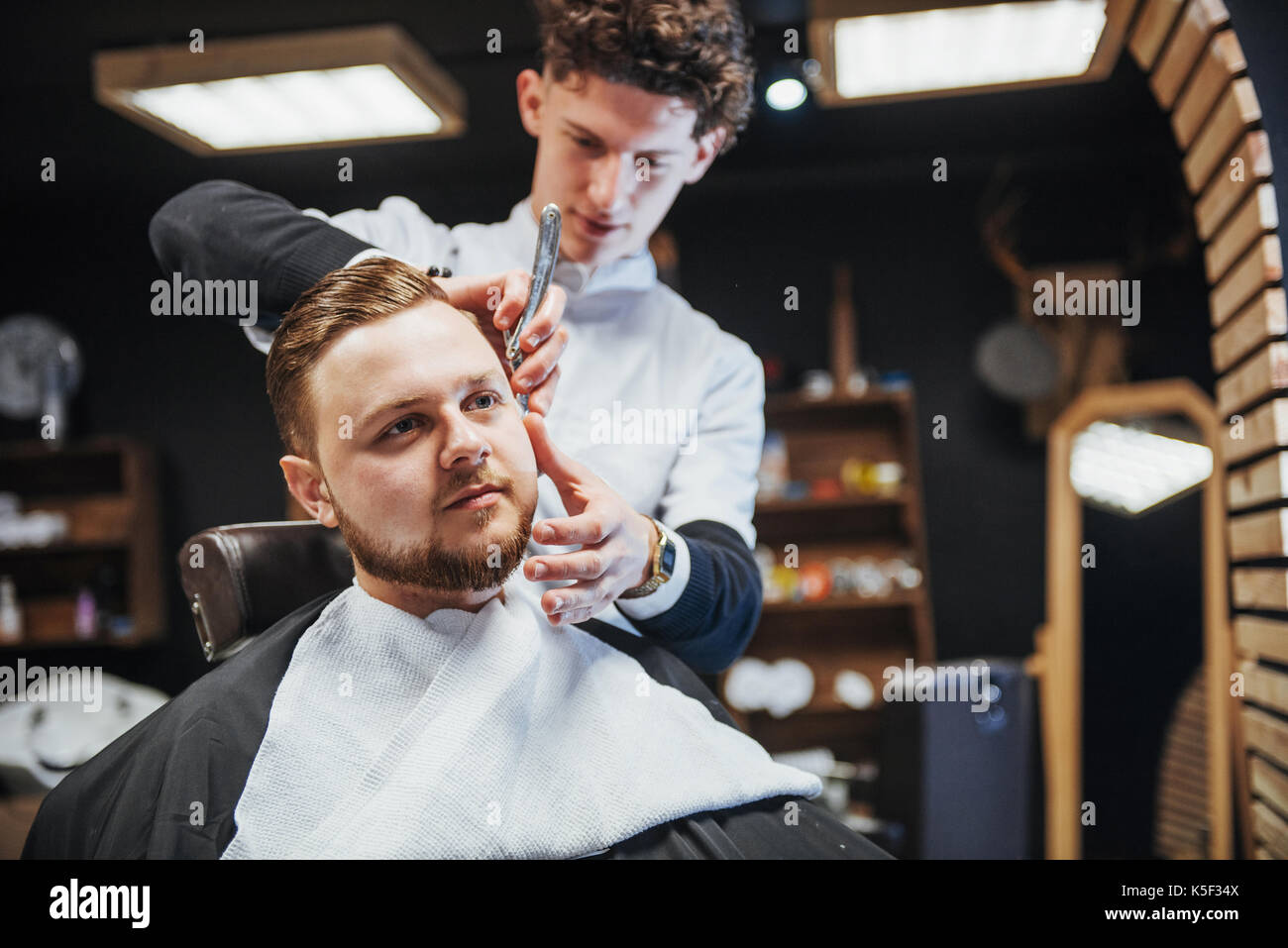 Men's hairstyling and haircutting in a barber shop or hair salon. - Stock Image