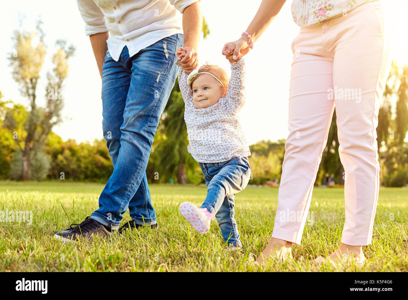The first steps of the baby.  A happy family. - Stock Image
