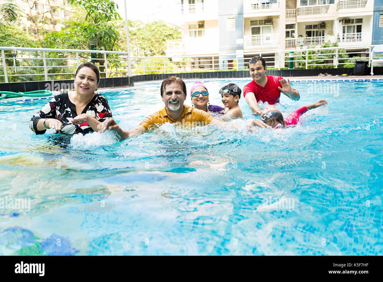 Big Family Bathing swimming pool having fun Real Estate Apartment House - Stock Image