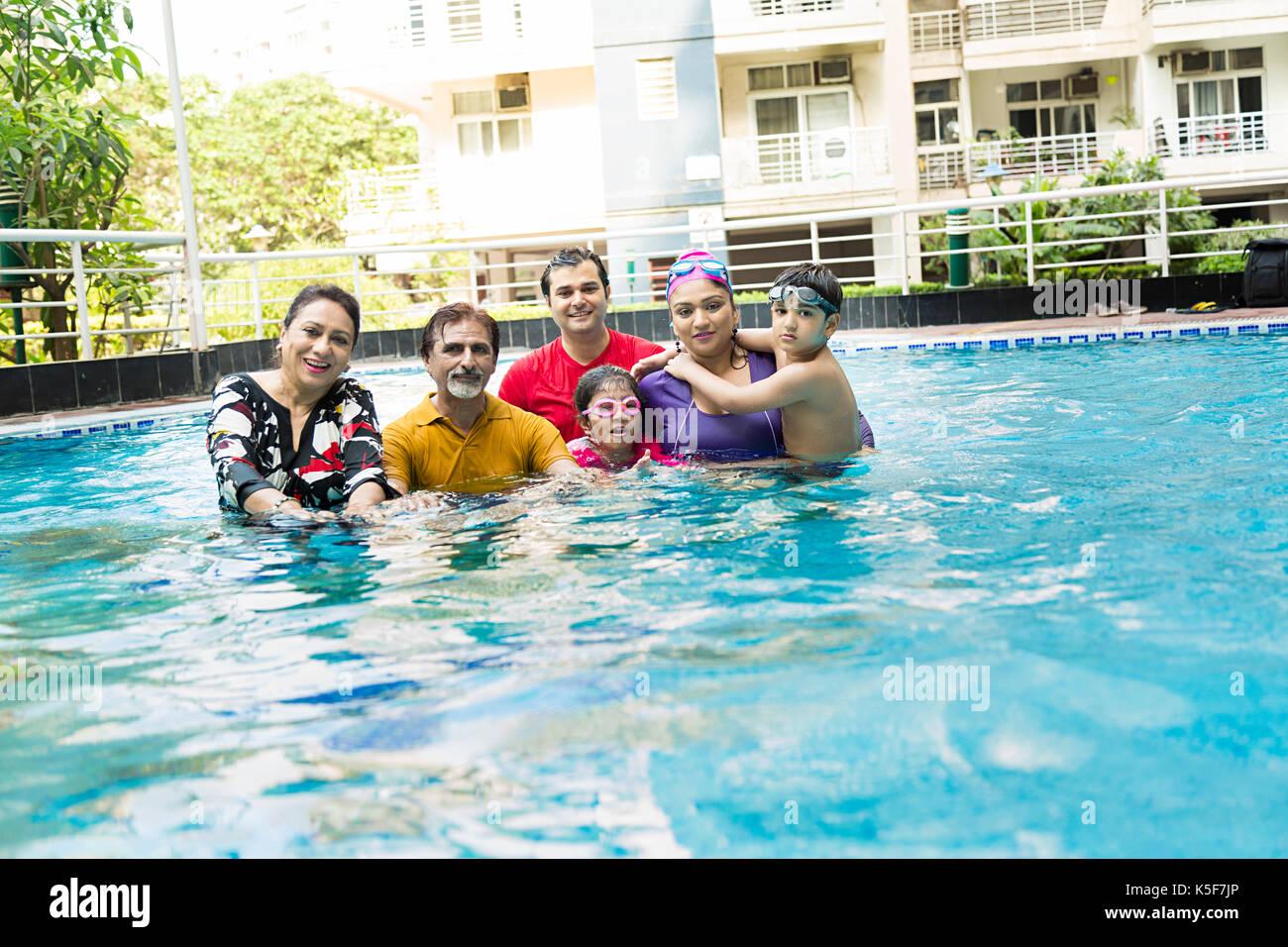 Big Family Bathing swimming pool having fun Real Estate Hotel - Stock Image