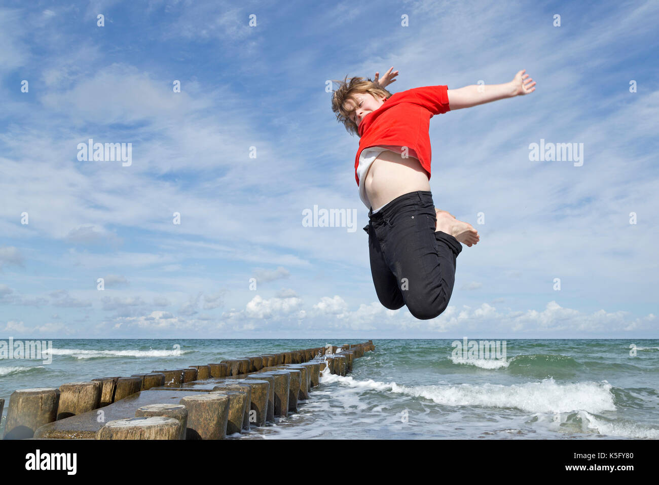 boy jumping at the beach, Ahrenshoop, Fischland, Mecklenburg-West Pomerania, Germany - Stock Image
