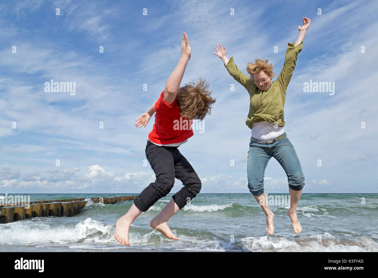 mother and son jumping at the beach, Ahrenshoop, Fischland, Mecklenburg-West Pomerania, Germany - Stock Image
