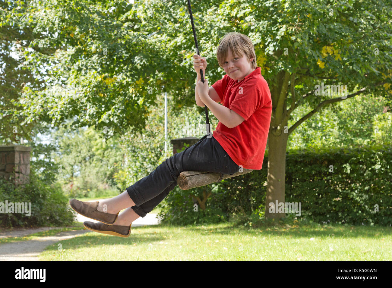 young boy swinging on a rope - Stock Image