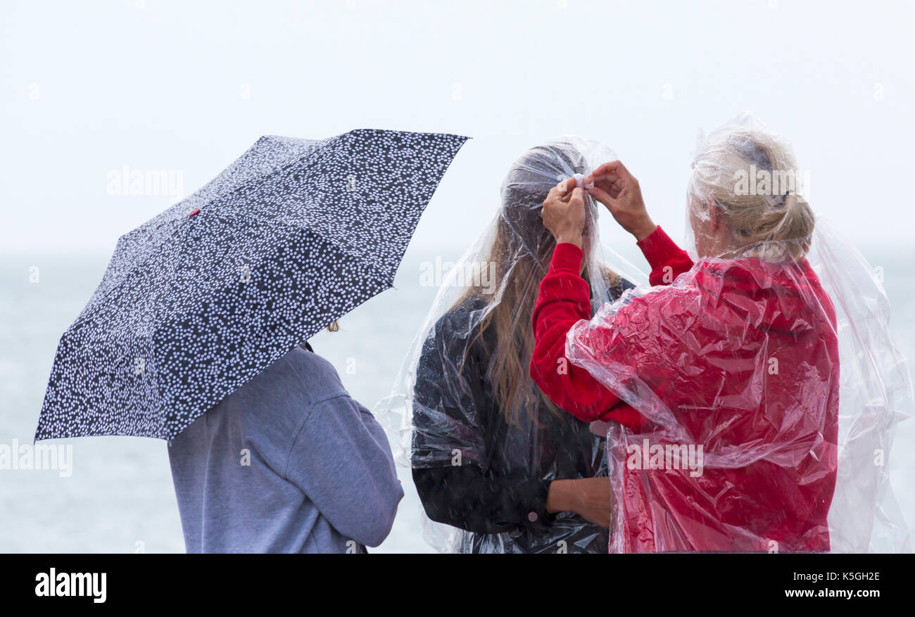 Swanage, Dorset, UK. 9th Sep, 2017. UK weather: heavy rain and thunder at Swanage. 3 people trying to keep dry, by sheltering under umbrella or wearing ponchos. Credit: Carolyn Jenkins/Alamy Live News - Stock Image