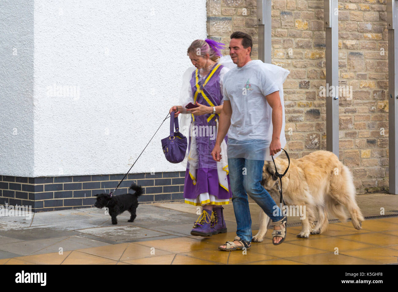Swanage, Dorset, UK. 9th Sep, 2017. UK weather: heavy rain and thunder at Swanage. Couple walking dogs along promenade wearing transparent ponchos for protection in the rain. Credit: Carolyn Jenkins/Alamy Live News - Stock Image