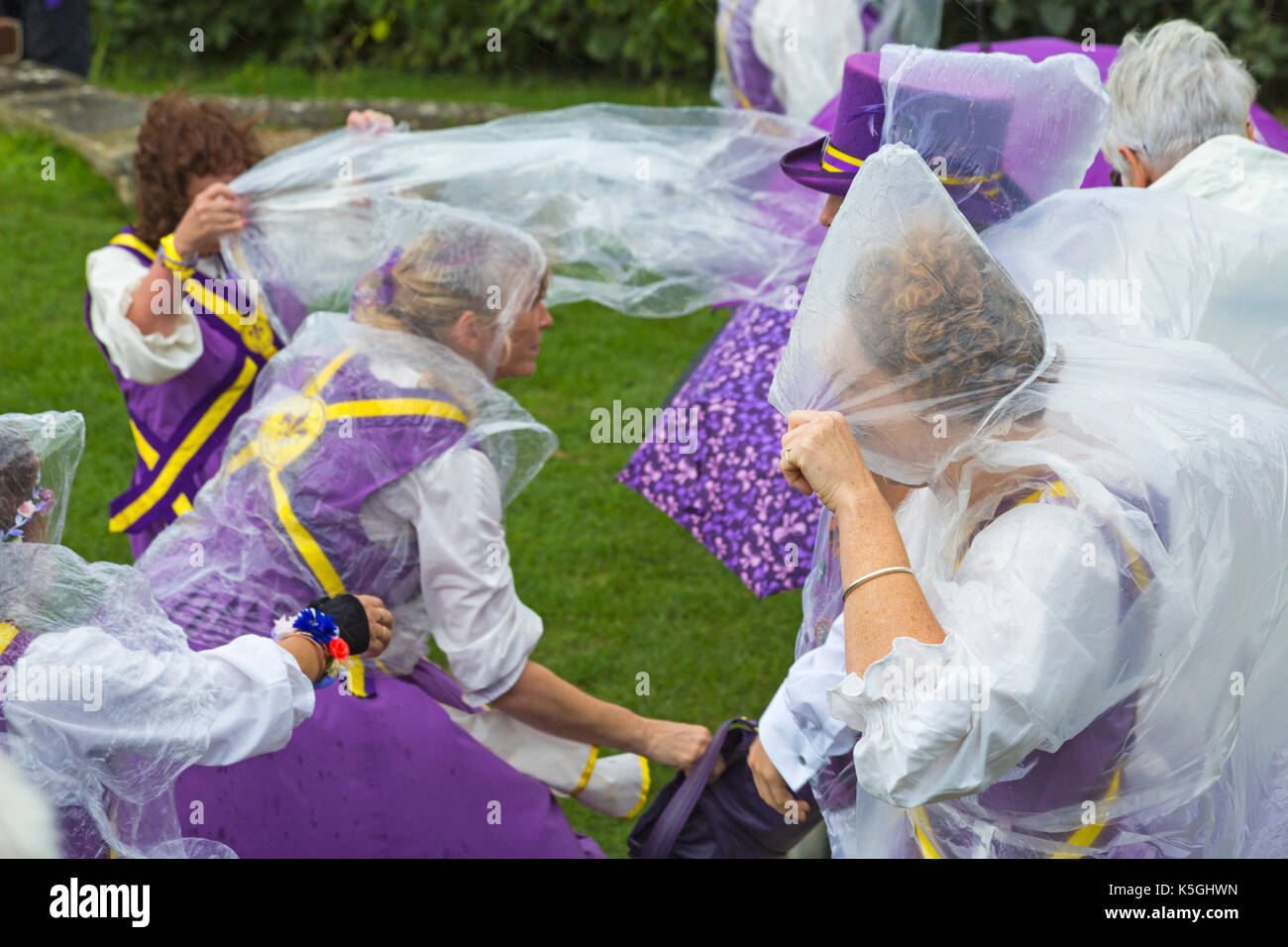 Swanage, Dorset, UK. 9th Sep, 2017. Crowds flock to the Swanage Folk Festival on the 25th anniversary to see the dance groups and music along the seafront. The mixed weather, sunshine and rain, doesn't deter their spirits.  Members of Fleur de Lys putting on ponchos. Credit: Carolyn Jenkins/Alamy Live News - Stock Image