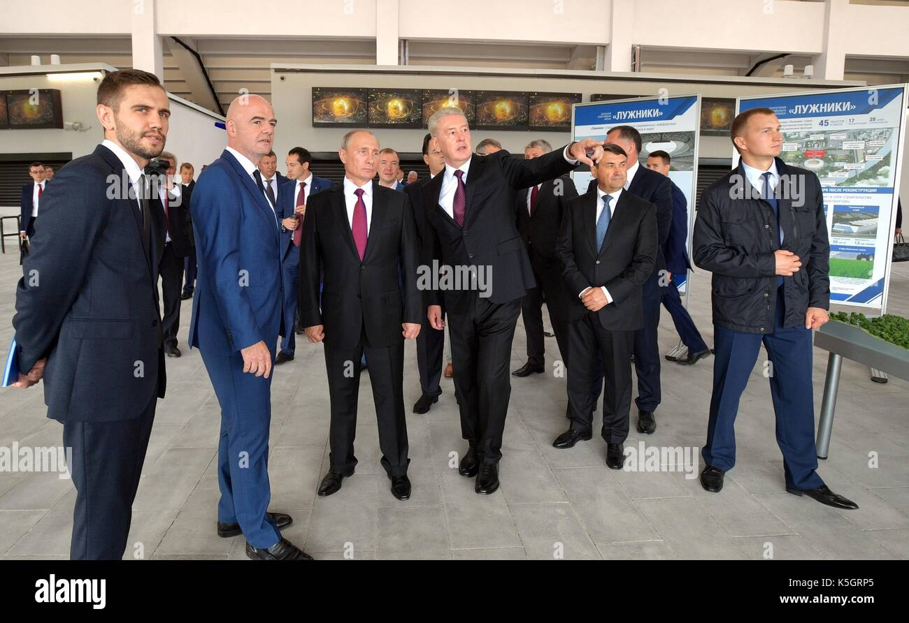 Russian President Vladimir Putin is shown around the newly renovated Luzhniki Grand Sports Arena by Moscow Mayor Sergei Sobyanin, right, and FIFA President Gianni Infantino, left, prior to the start of the FIFA World Cup Trophy Tour September 9, 2017 in Moscow, Russia. - Stock Image