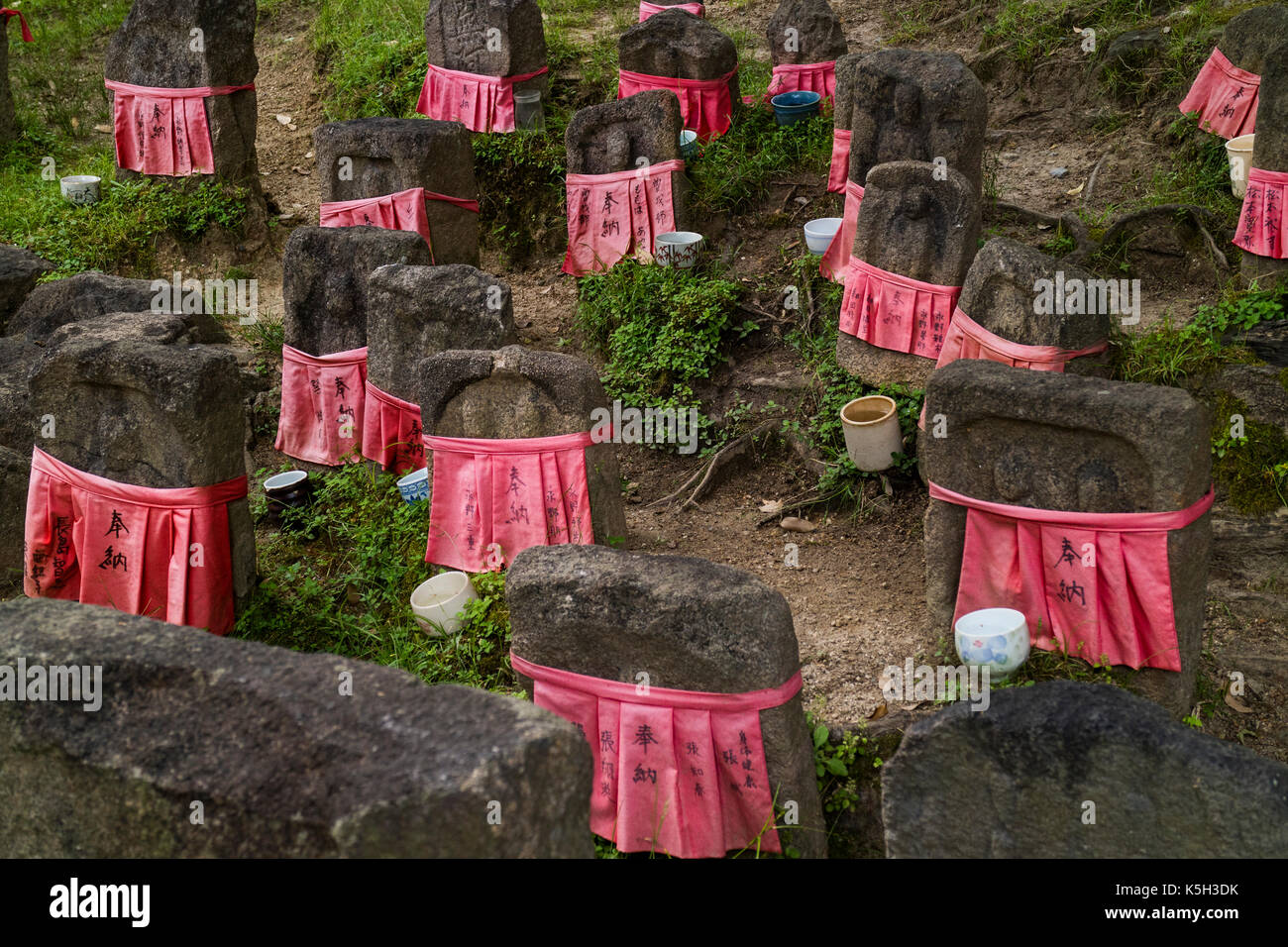Nara - Japan, May 30, 2017: Peaceful stone relegious Jizo statues with red skirts in the garden - Stock Image