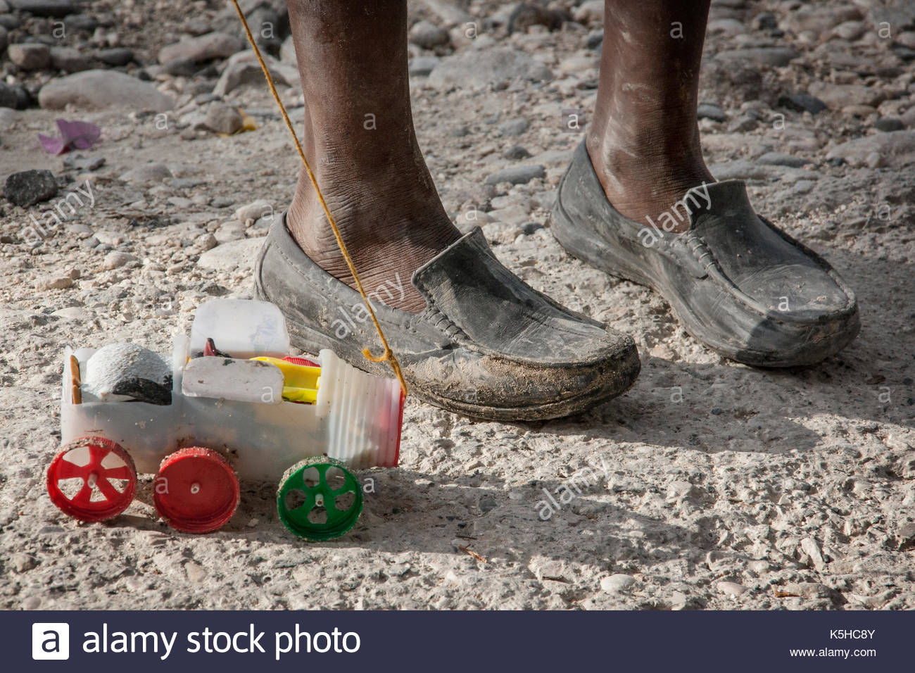 Home made toy held by a boy in the streets of Haiti Stock Photo
