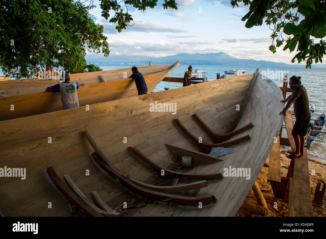 Boat builders observe their work on the beach at Bunaken Island, Sulawesi - Stock Image