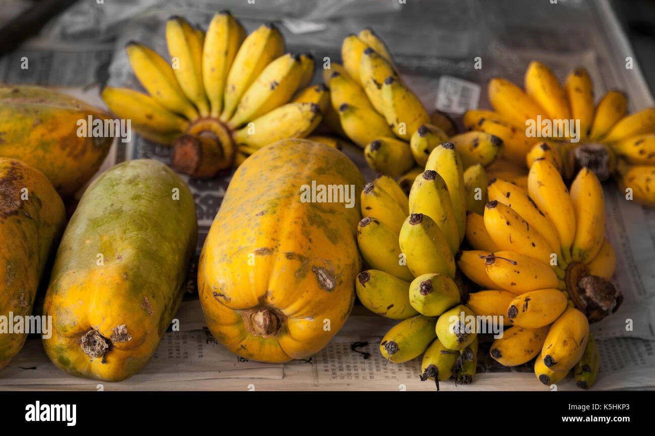Local bananas and papaya fruits on a market stall, Malaysia - Stock Image