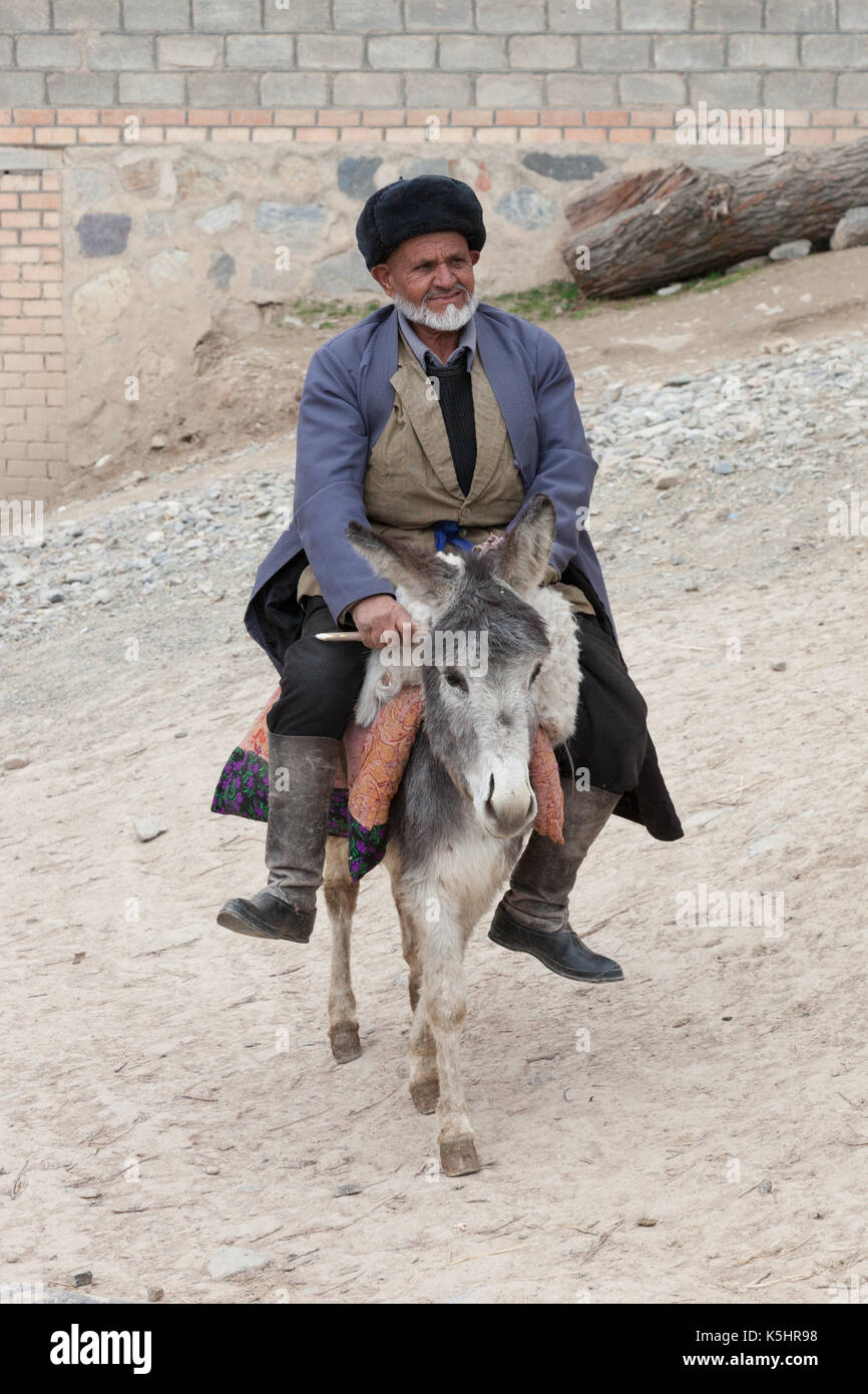 old man riding a donkey in a mountain village Stock Photo