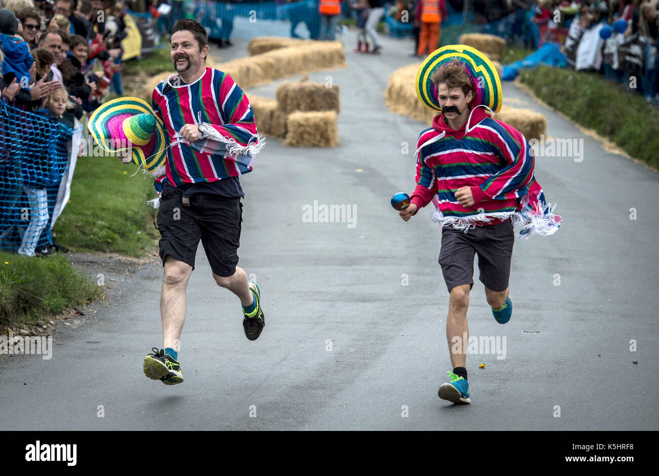 Men wearing ponchos and sombreros chase after a Donald Trump themed kart during the Gravity Grand Prix, a fundraising downhill kart race driven by gravity, following a short push at the start at Cookham Dean, Berkshire. - Stock Image