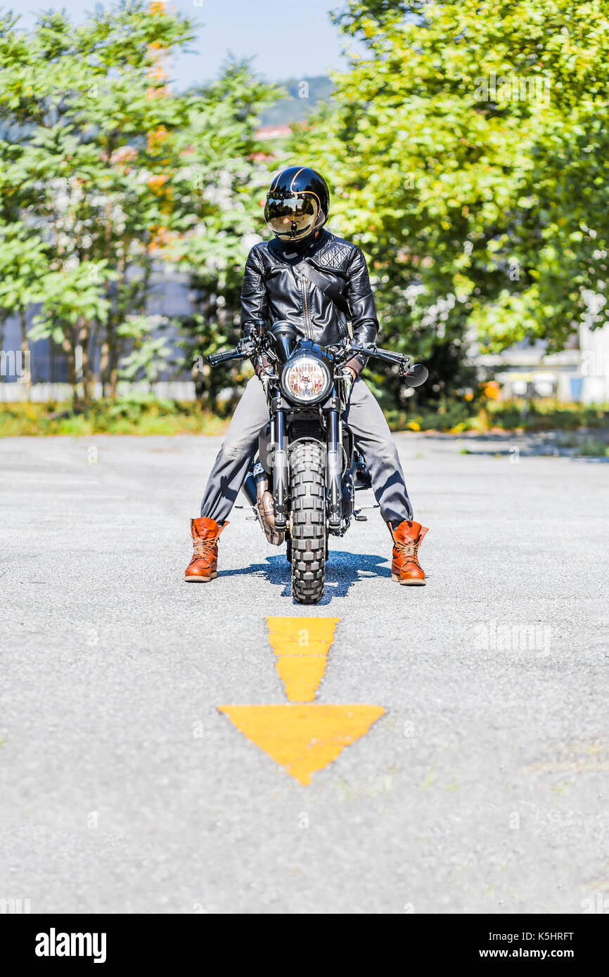 Cool looking motorcycle rider on custom made scrambler style cafe racer on the road with an arrow sign - Stock Image