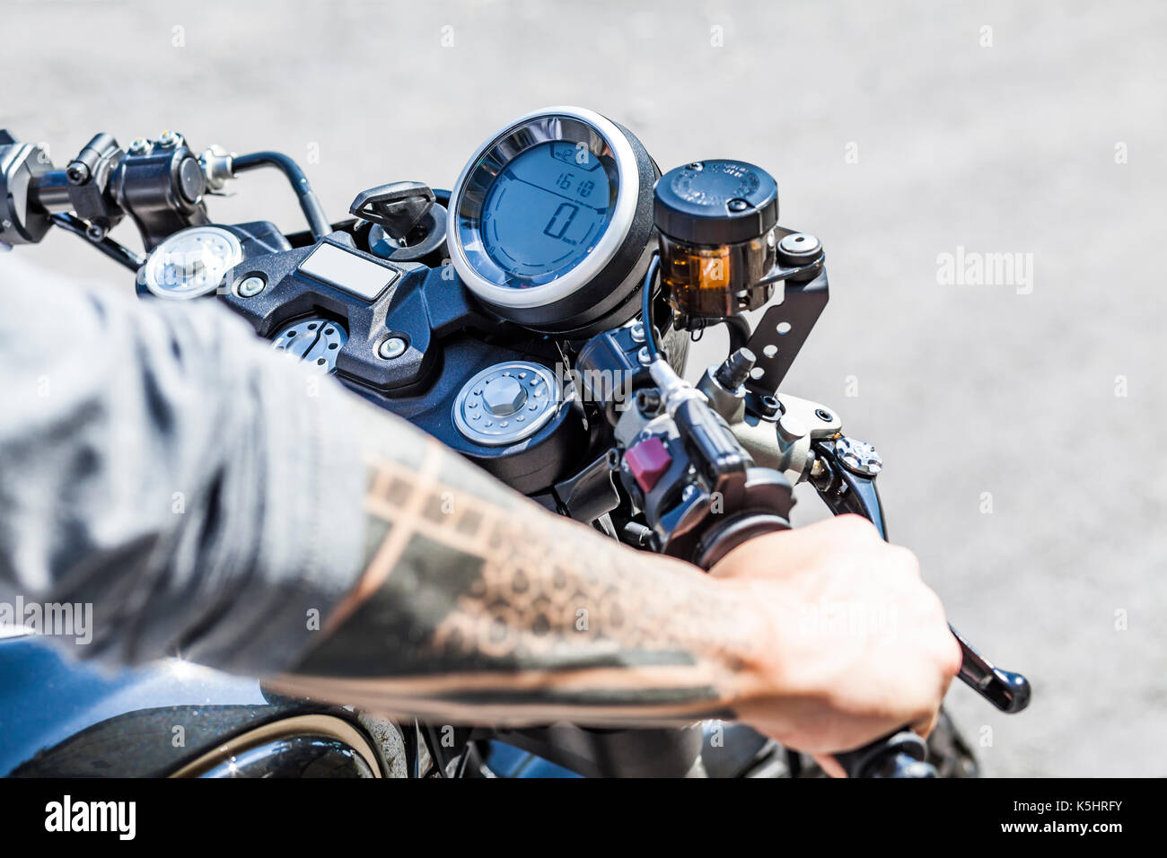 Cool looking tattoos on arms of motorcycle rider on custom made scrambler style cafe racer - Stock Image