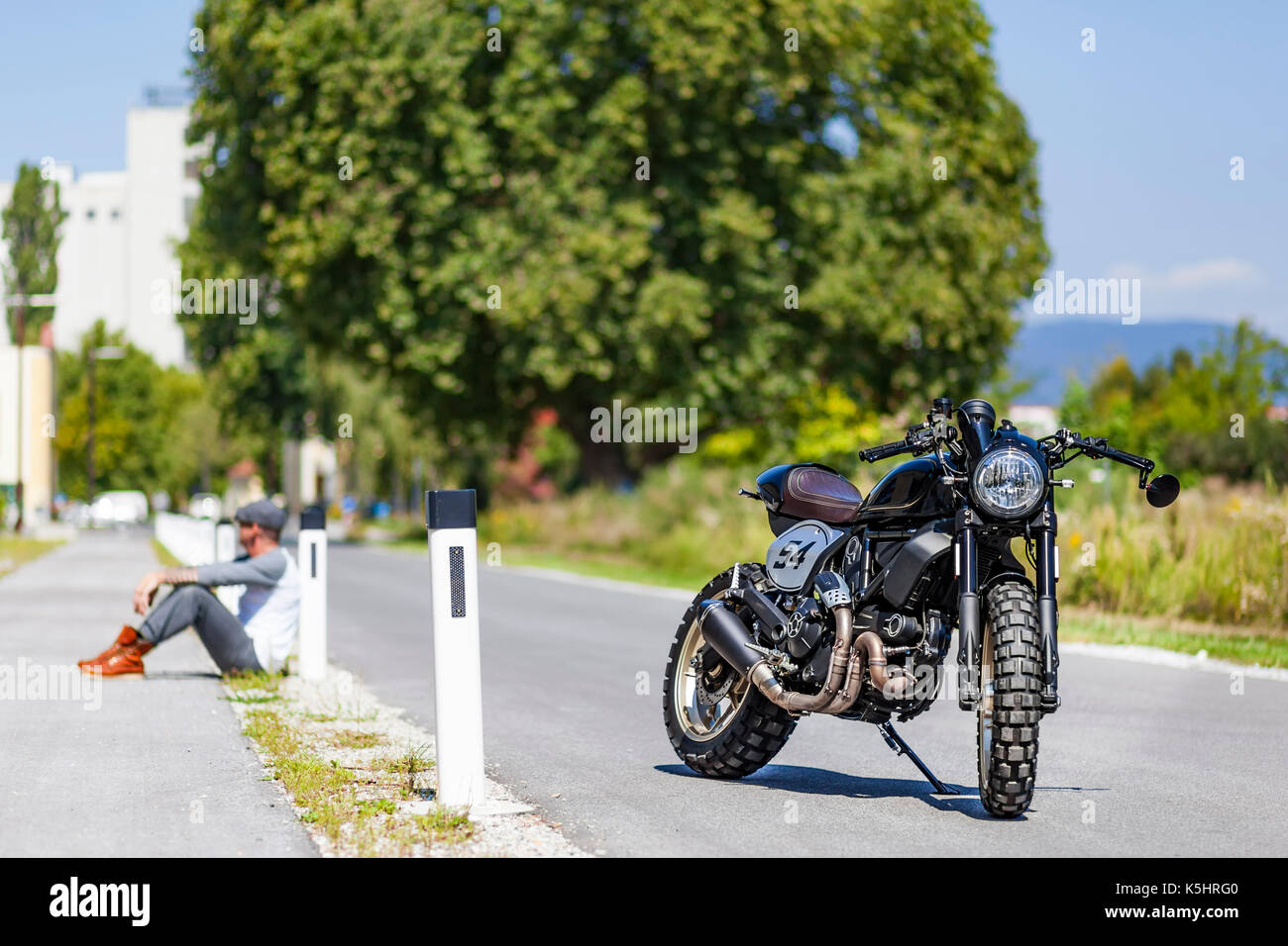 Cool looking motorcycle rider sitting near custom made scrambler style cafe racer - Stock Image