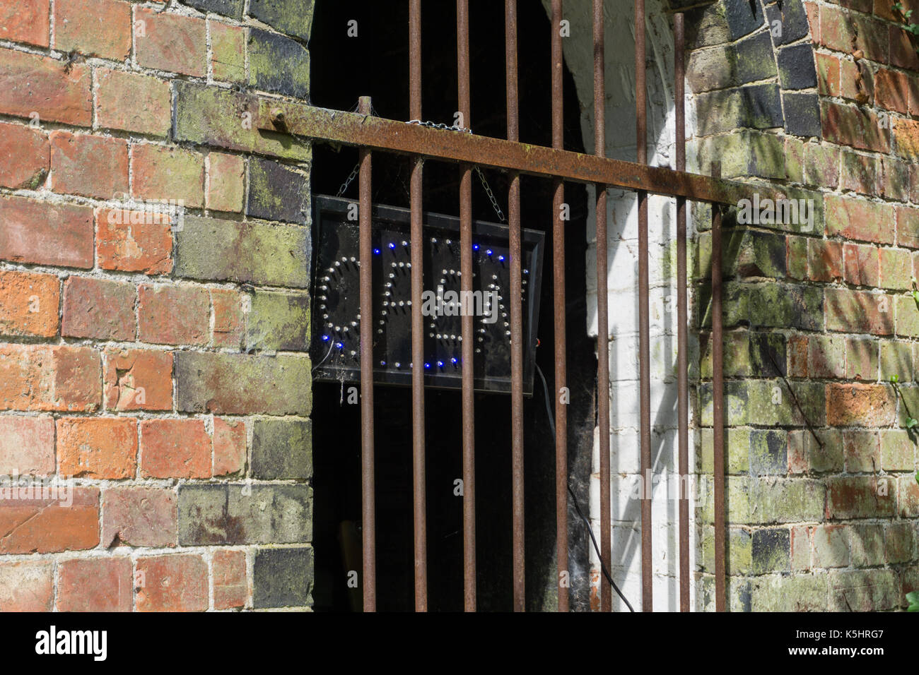 Electrically lit Open sign located behind a barred window. - Stock Image