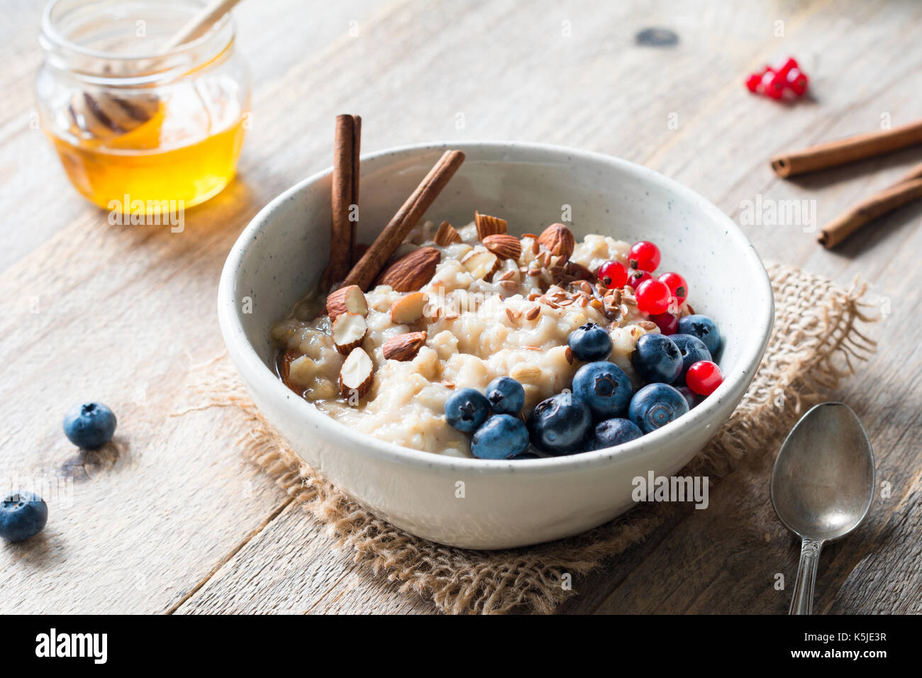 Oatmeal porridge with blueberries, almonds, cinnamon, honey, linseeds and red currants in bowl. Super food for healthy nutritious breakfast - Stock Image