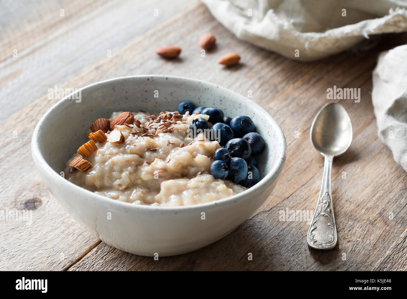 Oatmeal porridge with blueberries, almonds, linseeds in bowl on wooden table. Super food for healthy nutritious breakfast - Stock Image