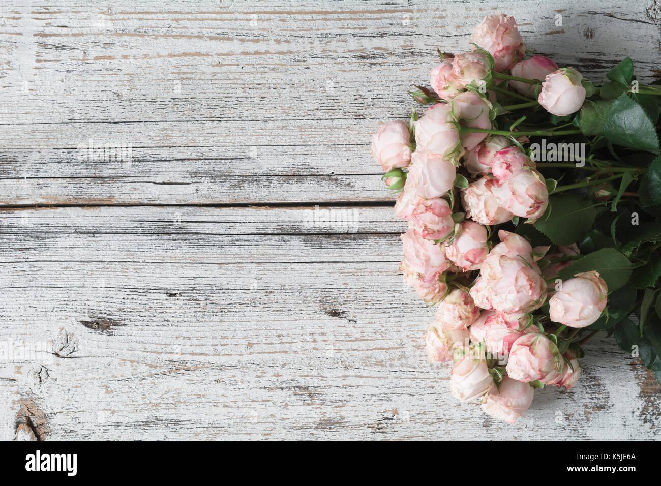 Pink roses on vintage wooden background  Floral frame