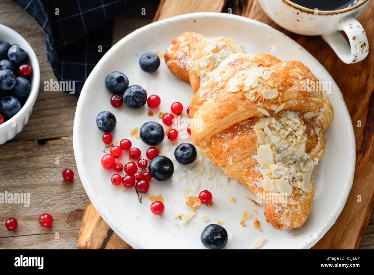 Fresh croissant, blueberries and red currants on white plate. Continental breakfast. Horizontal composition - Stock Image