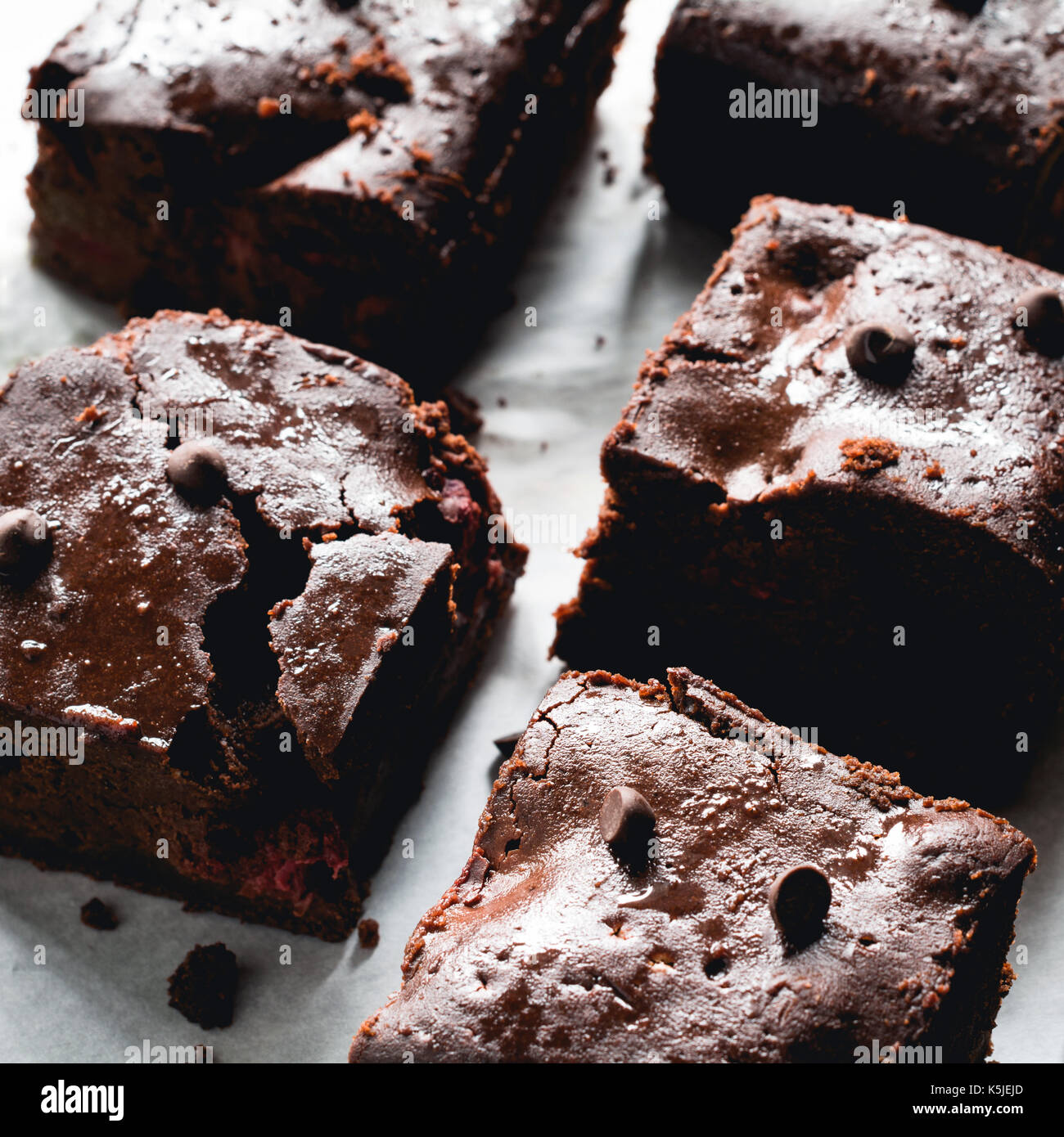 Dark chocolate brownies on baking paper. Closeup view square crop - Stock Image