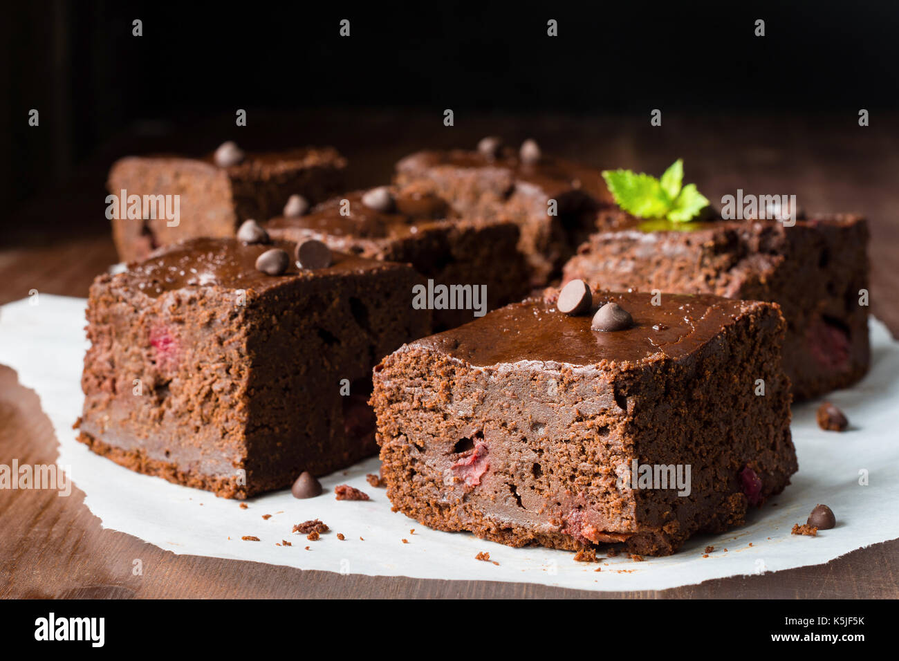 Dark chocolate brownies decorated with mint leaf on wooden table. Closeup view horizontal composition - Stock Image