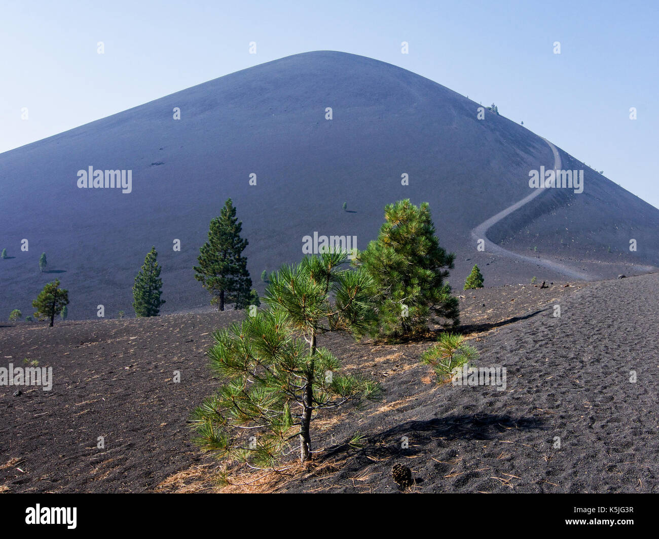 Cinder Cone trail, Lassen Volcanic National Park, on a smoky day, featuring the lava bed, the bare, rugged terrain and a few pine trees - Stock Image