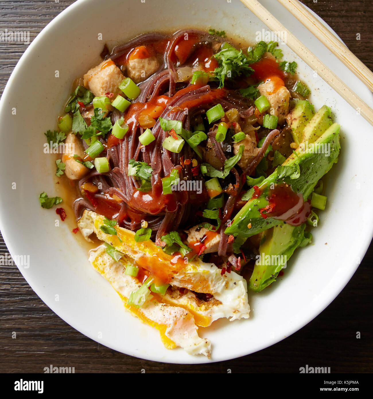 White bowl of chicken and veggie Pho with egg, avocado and sriracha - Stock Image