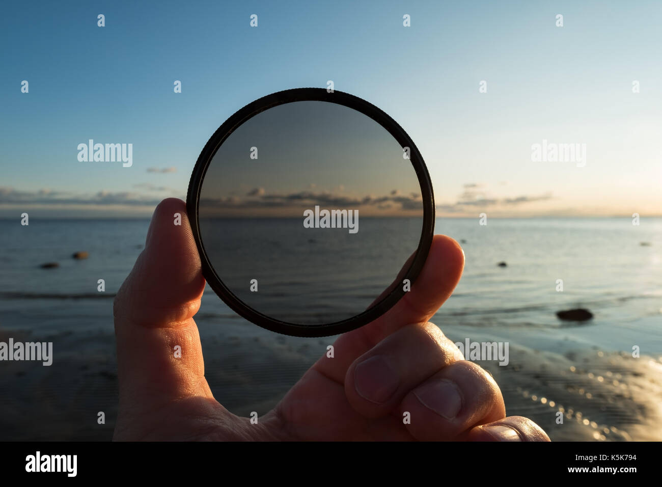 Man holding gradient neutral density ND filter on background of summer sunset - Stock Image