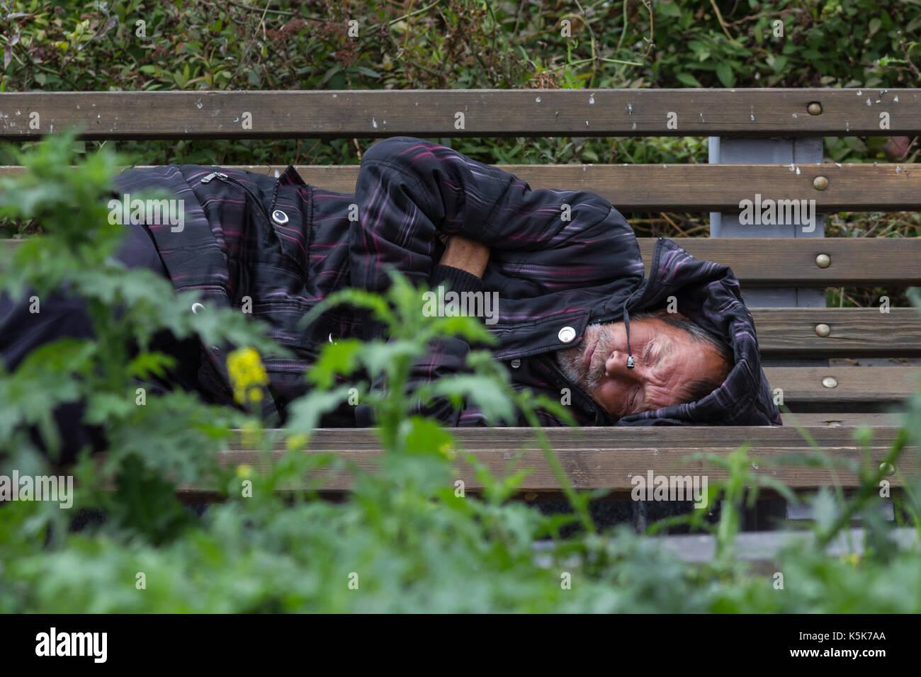 KAZAN, RUSSIA - 9 SEPTEMBER 2017: homeless alcoholic beggar man is sleeping on bench in park - Stock Image