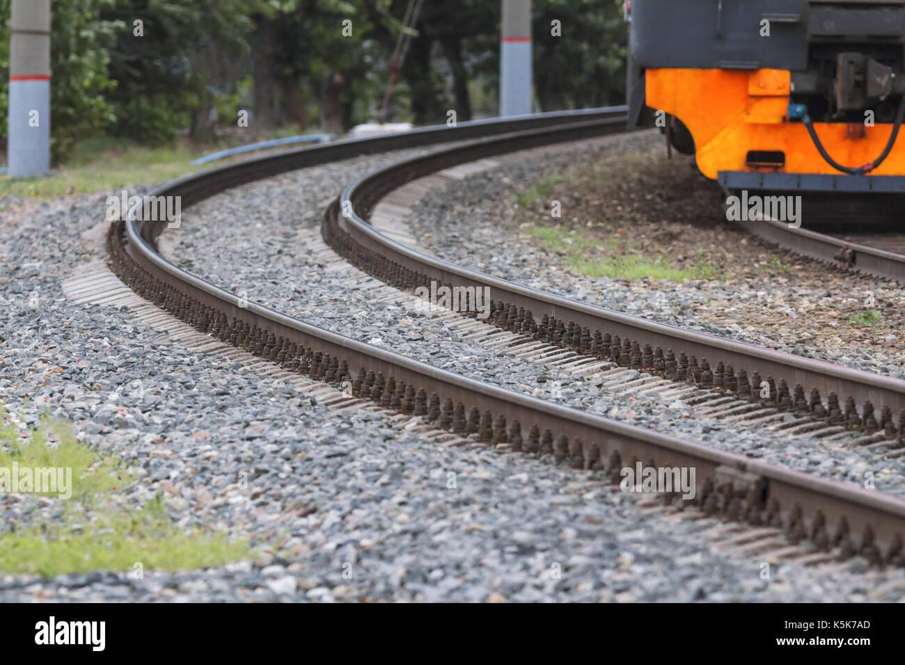 Curving railway tracks on crushed stone and orange train, telephoto - Stock Image