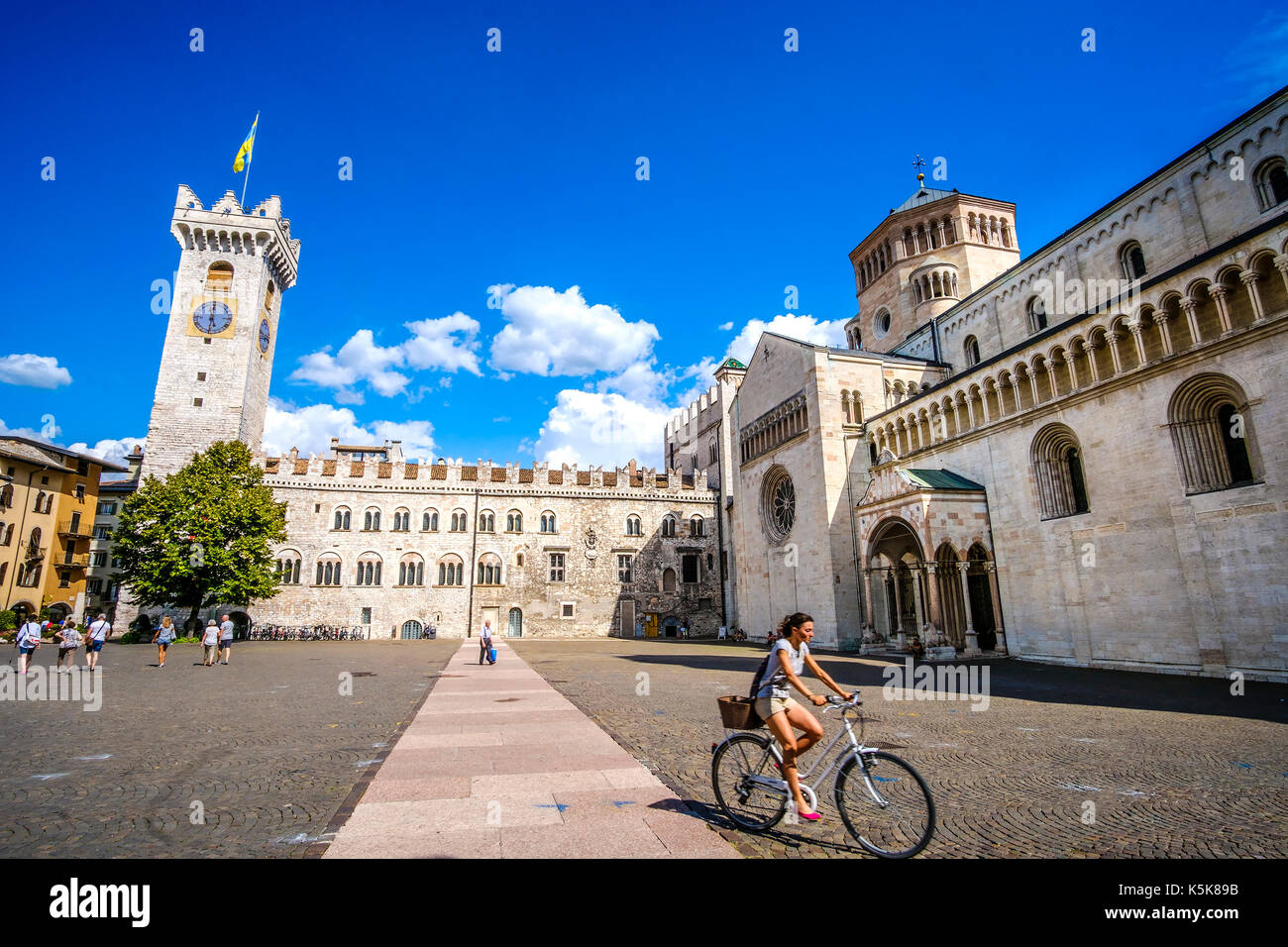 Trento, Italy, 14 Aug 2017 - A young woman go in bicycle in the middle of Piazza Duomo in Trento. Travel by bicycle in Italy, cultural trip in Italy - Stock Image