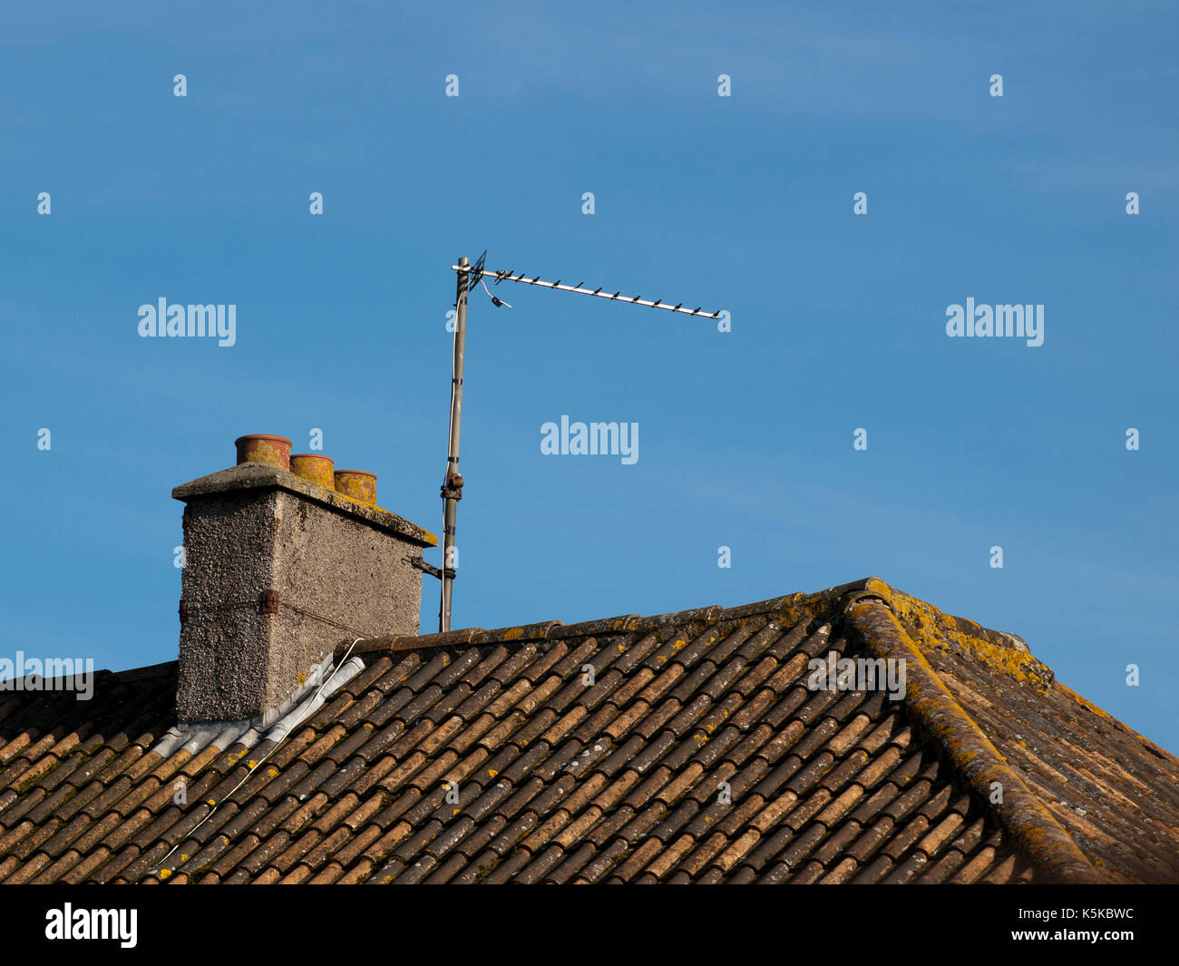 TV Aerial on a rooftop set against a clear blue sky - Stock Image