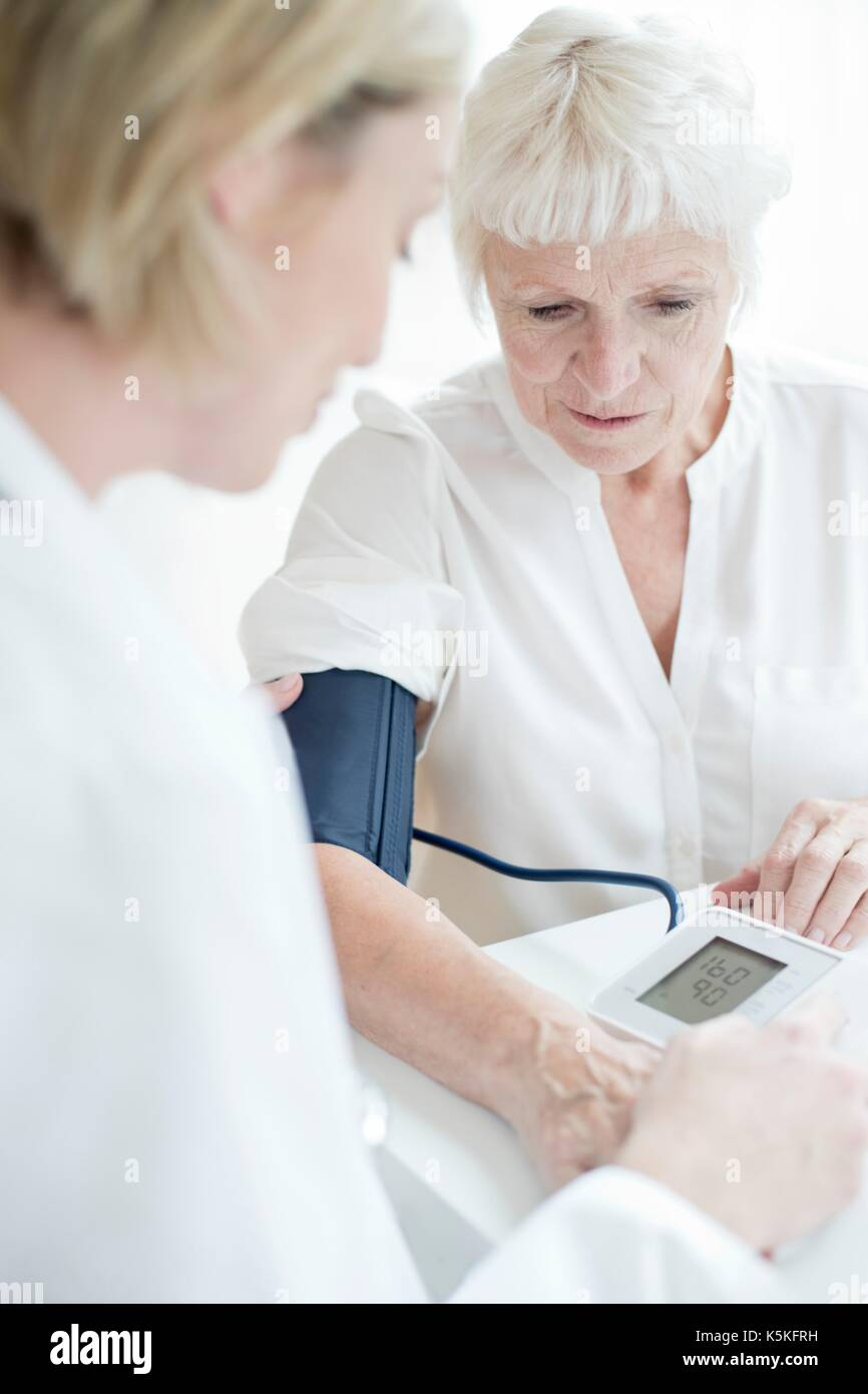 Senior woman having blood pressure taken. - Stock Image