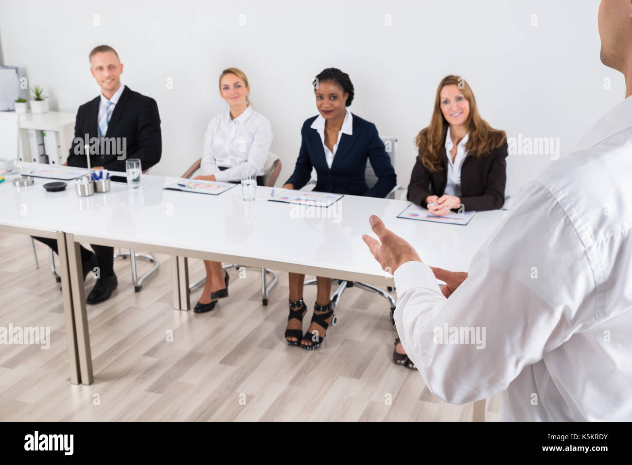Businessperson Having Discussion With Colleague In Office - Stock Image