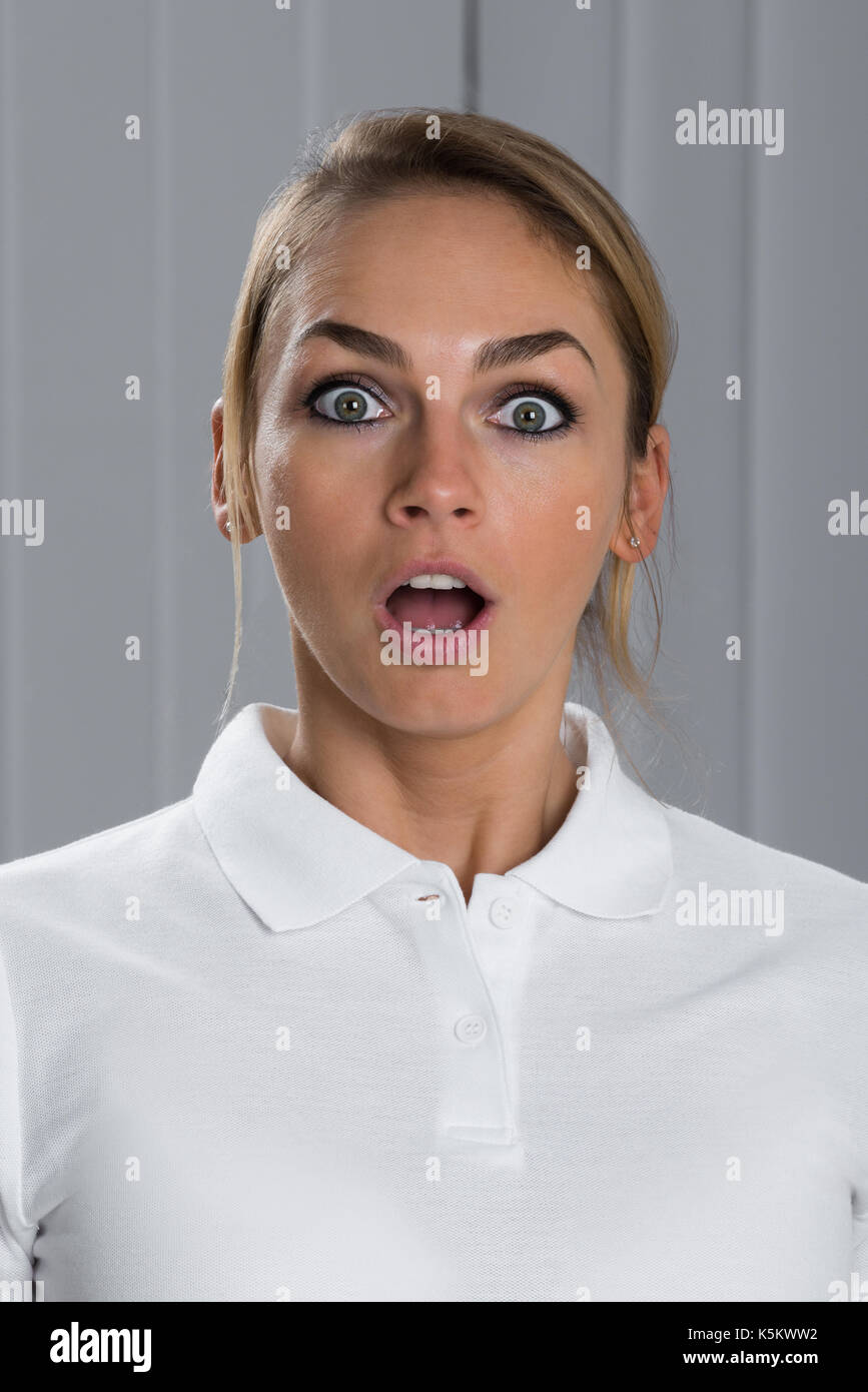 Portrait Of Surprised Young Beautiful Woman In White T-shirt - Stock Image