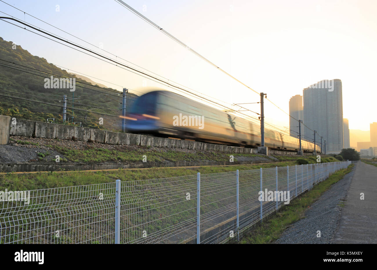 Good Morning :  under the bright, first train running / speed up on railway in hong kong, china, Tung Chung area, Lantau Island cityscape - Stock Image