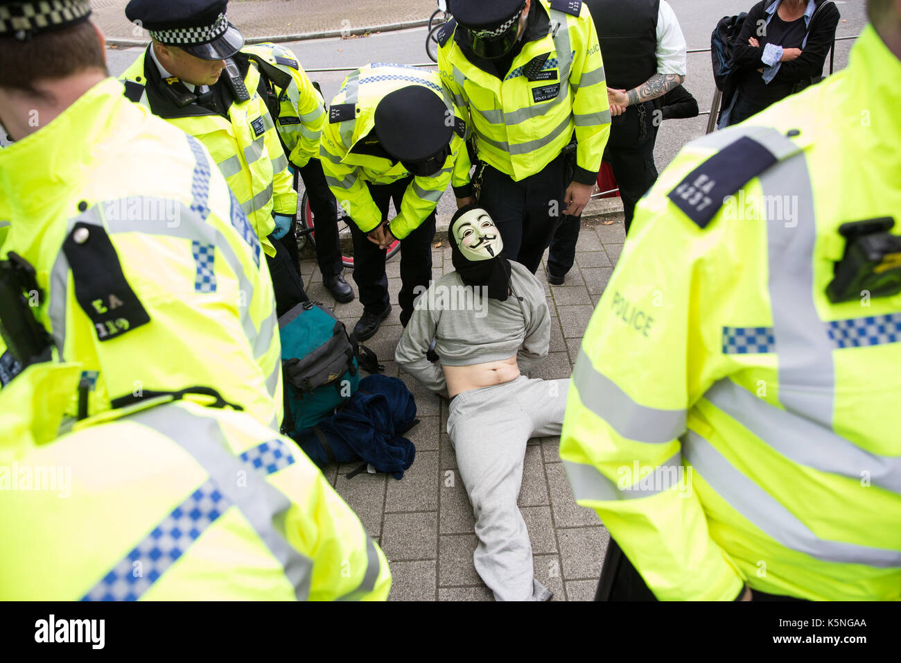 London, UK. 9th September, 2017. Police officers stop and search a man wearing a Guy Fawkes mask during a protest by activists from many different campaign and faith groups outside the ExCel Centre against the arms trade and the arms fair to be held at the venue next week. The man was released following the search because nothing was found. DSEI is the world's largest arms fair and military delegations invited by the British government include states named by the Foreign Office as a 'human rights priority' , namely Bahrain, Colombia, Egypt, Pakistan and Saudi Arabia. Credit: Mark Kerri - Stock Image
