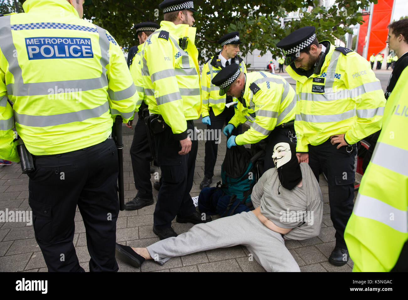 London, UK. 9th September, 2017. Police officers stop and search a man wearing a Guy Fawkes mask during a protest Stock Photo