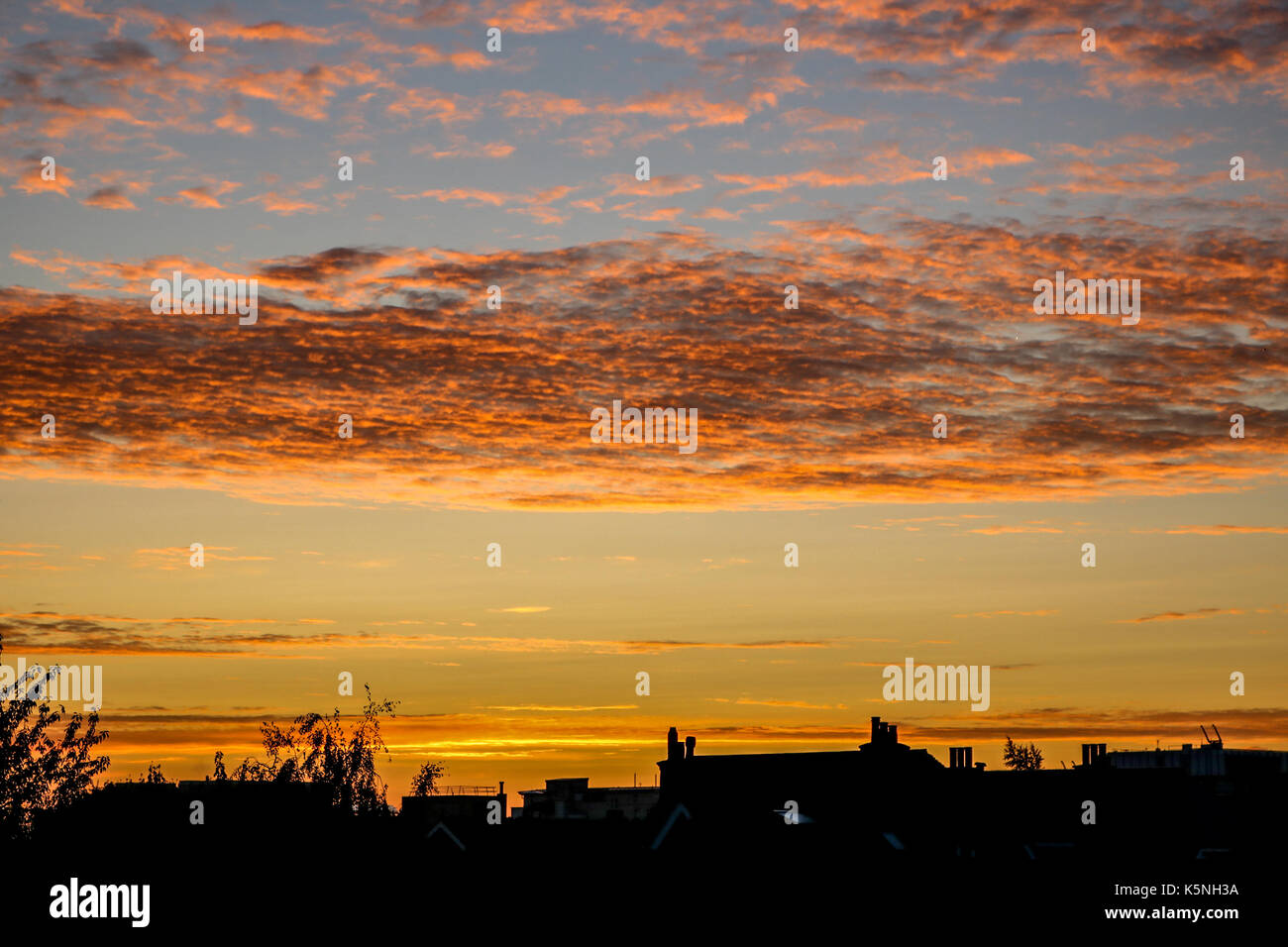 London UK.  10th September 2017.  Residential rooftop buildings are silhouetted against a beautiful  autumn sunrise Stock Photo