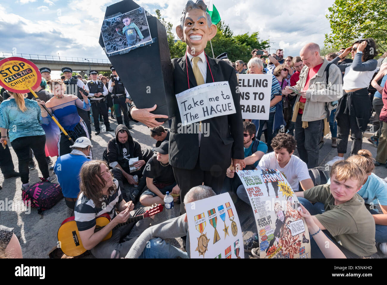 London, UK. 9th Sep, 2017. London, UK. 9th September 2017. Protesters, including a man in a TOny Blair mas with a placard 'Take me to the HAGUE' and a small coffin block the road at the Festival of Resistance at the East gate of the worlds's largest arms fair, DSEI, the Defence & Security Equipment International. The arms fair is backed by the UK government and is where arms companies and arms dealers sell weapons to countries around the world including many repressive regimes. Police tried to clear the road and made several arrests. Peter Marshall Images Live (Credit Image: © Peter Mar Stock Photo
