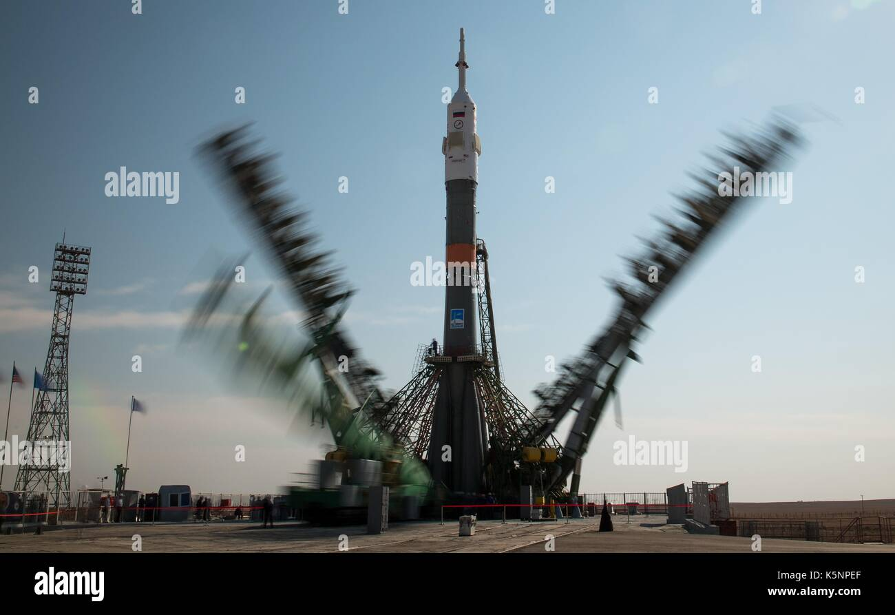 The Russian Soyuz rocket and Soyuz MS-06 spacecraft are positioned on the launch pad as the gantry arms close in - Stock Image