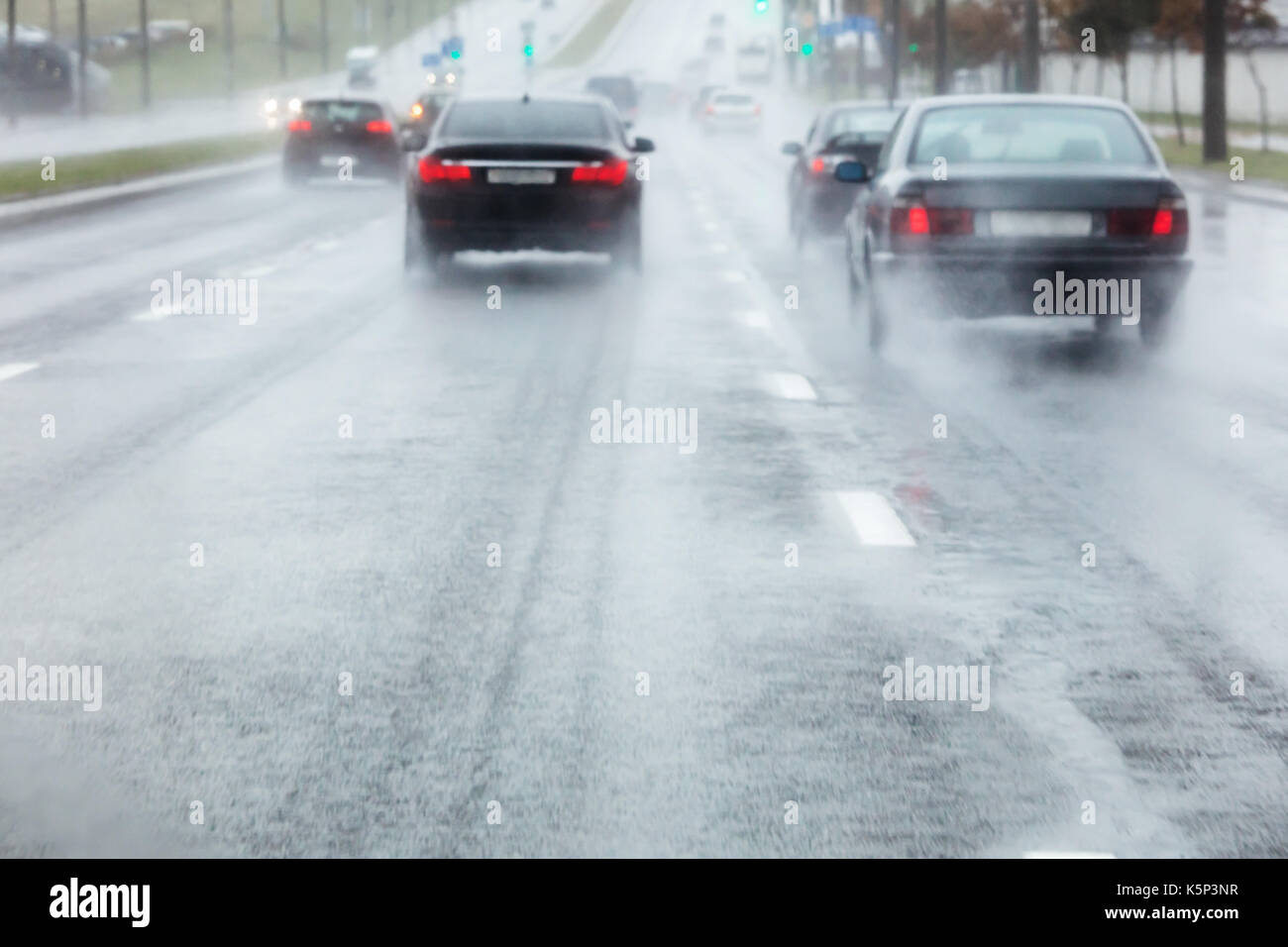 cars moving in wet road with water spraying from the wheels. blurred view through windshield. - Stock Image