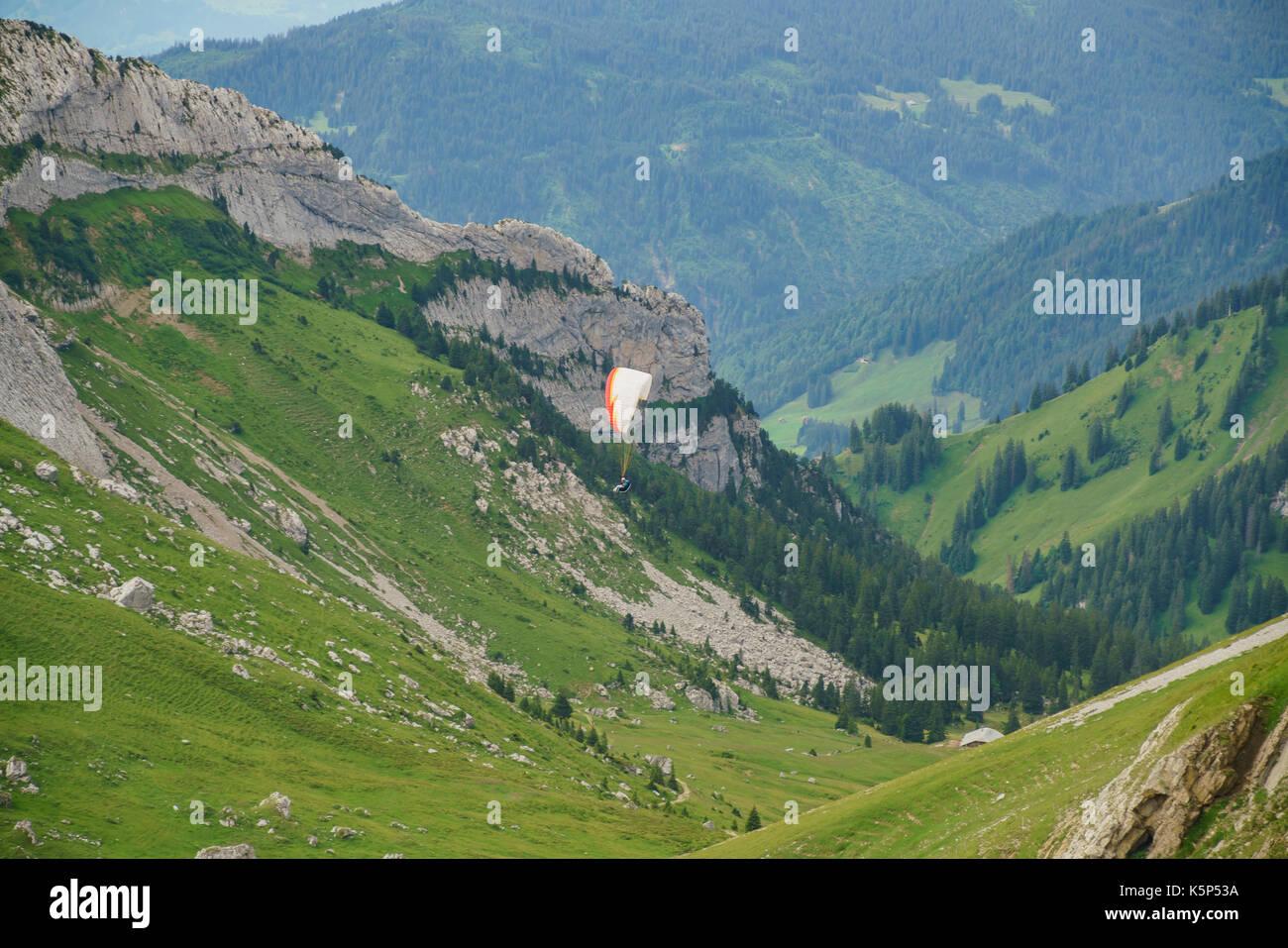 Man playing hang gliding over Mount Pilatus, Lucerne, Switzerland - Stock Image