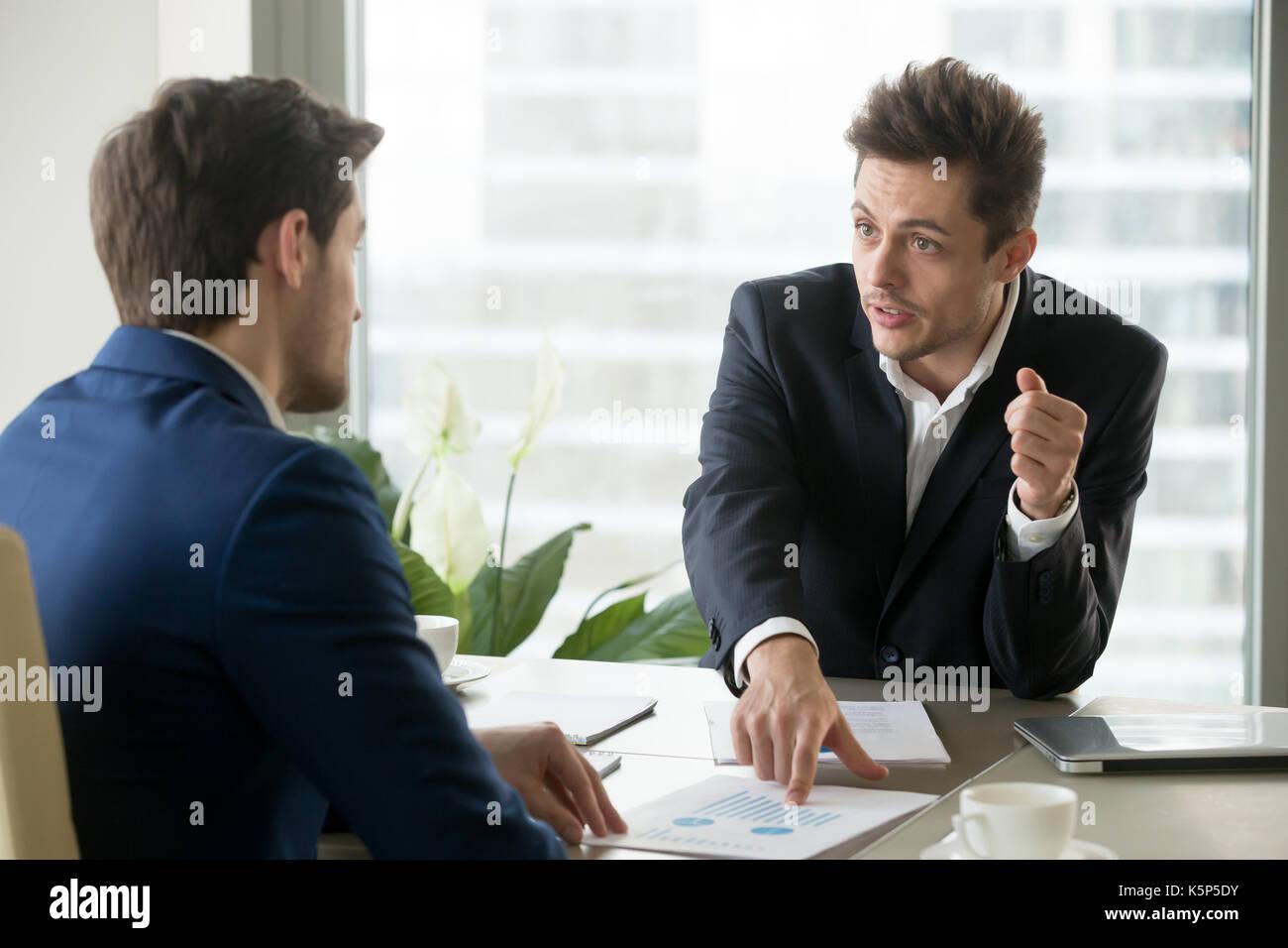 Entrepreneurs discussing business plan on meeting - Stock Image